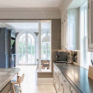 This is an example of an expansive transitional u-shaped eat-in kitchen in Toronto with an undermount sink, raised-panel cabinets, grey cabinets, soapstone benchtops, grey splashback, marble splashback, stainless steel appliances, marble floors, with island, beige floor and black benchtop.