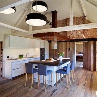 ウィルトシャーの中サイズのインダストリアルスタイルのおしゃれなキッチン (一体型シンク、フラットパネル扉のキャビネット、白いキャビネット、ラミネートカウンター、白いキッチンパネル、ガラス板のキッチンパネル、シルバーの調理設備の、無垢フローリング) の写真