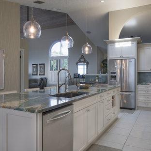 タンパの中サイズのビーチスタイルのおしゃれなキッチン (アンダーカウンターシンク、落し込みパネル扉のキャビネット、白いキャビネット、オニキスカウンター、青いキッチンパネル、ガラスタイルのキッチンパネル、シルバーの調理設備の) の写真