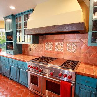 Idéer för ett rustikt l-kök, med en undermonterad diskho, luckor med upphöjd panel, blå skåp, kaklad bänkskiva, flerfärgad stänkskydd, stänkskydd i keramik, rostfria vitvaror, klinkergolv i terrakotta och en köksö