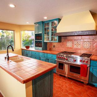 フェニックスのラスティックスタイルのおしゃれなキッチン (アンダーカウンターシンク、レイズドパネル扉のキャビネット、青いキャビネット、タイルカウンター、マルチカラーのキッチンパネル、セラミックタイルのキッチンパネル、シルバーの調理設備、テラコッタタイルの床) の写真