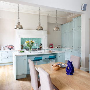 Design ideas for a classic u-shaped kitchen in Edinburgh with a submerged sink, shaker cabinets, white cabinets, blue splashback, stainless steel appliances, light hardwood flooring, an island and beige floors.