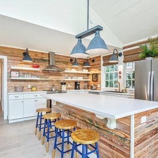 Réalisation d'une cuisine ouverte marine en L avec un placard avec porte à panneau encastré, des portes de placard en bois vieilli, une crédence marron, une crédence en bois, un électroménager en acier inoxydable, un îlot central, un sol gris et un plan de travail blanc.