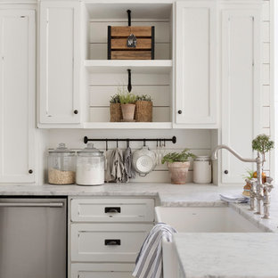 This is an example of a medium sized rural u-shaped kitchen/diner in Minneapolis with a belfast sink, white cabinets, white splashback, wood splashback, an island, white worktops, recessed-panel cabinets and stainless steel appliances.