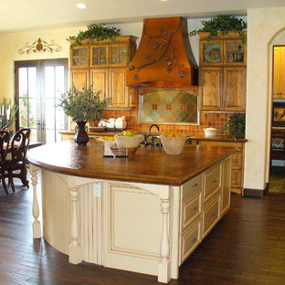 This is an example of a country l-shaped eat-in kitchen in Denver with raised-panel cabinets, beige cabinets, marble benchtops, orange splashback, mosaic tile splashback, panelled appliances, dark hardwood floors and with island.