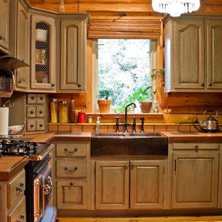Стильный дизайн: п-образная кухня-гостиная среднего размера в стиле кантри с раковиной в стиле кантри, фасадами с выступающей филенкой, искусственно-состаренными фасадами, столешницей из плитки, бежевым фартуком, фартуком из керамической плитки, черной техникой, паркетным полом среднего тона, коричневым полом и красной столешницей без острова - последний тренд