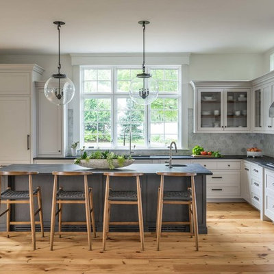 Inspiration for a large transitional l-shaped medium tone wood floor kitchen remodel in Boston with white cabinets, soapstone countertops, gray backsplash, ceramic backsplash, an island, glass-front cabinets and a single-bowl sink
