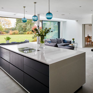 This is an example of a contemporary galley open plan kitchen in Kent with flat-panel cabinets, black cabinets, black appliances, concrete flooring, an island, grey floors and beige worktops.