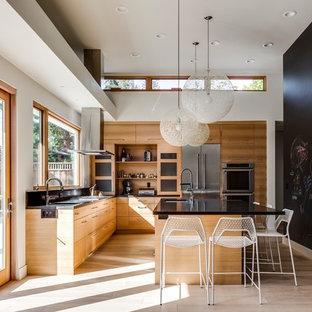 Cette photo montre une grande cuisine américaine tendance en L avec un évier encastré, un placard à porte plane, des portes de placard en bois brun, une crédence noire, un électroménager en acier inoxydable, un sol en bois clair, un îlot central, un sol beige et un plan de travail noir.