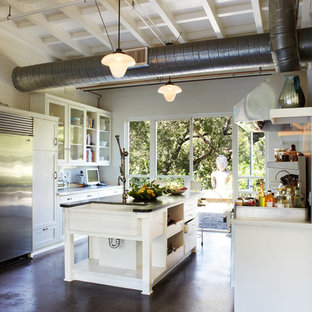 Large industrial open concept kitchen designs - Example of a large urban single-wall concrete floor open concept kitchen design in Orange County with a farmhouse sink, glass-front cabinets, white cabinets, solid surface countertops, metallic backsplash, metal backsplash, stainless steel appliances and an island