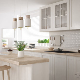 This is an example of a mid-sized shabby-chic style single-wall separate kitchen in Miami with a drop-in sink, louvered cabinets, white cabinets, wood benchtops, white splashback, porcelain splashback, stainless steel appliances, light hardwood floors, with island and beige floor.