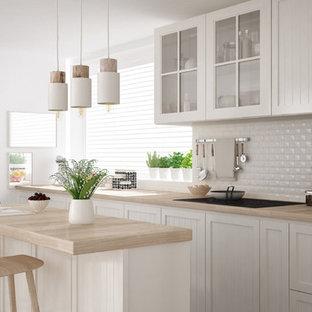 マイアミの中サイズのシャビーシック調のおしゃれなキッチン (ドロップインシンク、ルーバー扉のキャビネット、白いキャビネット、木材カウンター、白いキッチンパネル、磁器タイルのキッチンパネル、シルバーの調理設備の、淡色無垢フローリング、ベージュの床) の写真
