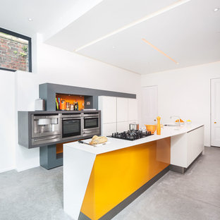 Design ideas for a large modern galley kitchen/diner in Glasgow with a single-bowl sink, flat-panel cabinets, white cabinets, orange splashback, stainless steel appliances, concrete flooring and an island.