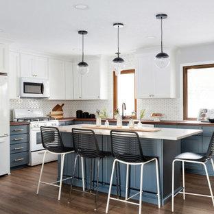 ミネアポリスの広いトランジショナルスタイルのおしゃれなキッチン (アンダーカウンターシンク、フラットパネル扉のキャビネット、青いキャビネット、木材カウンター、白いキッチンパネル、モザイクタイルのキッチンパネル、白い調理設備、クッションフロア、茶色い床、茶色いキッチンカウンター) の写真