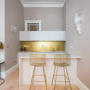 This is an example of a medium sized contemporary single-wall kitchen in London with a submerged sink, flat-panel cabinets, white cabinets, metallic splashback, light hardwood flooring, beige floors and white worktops.