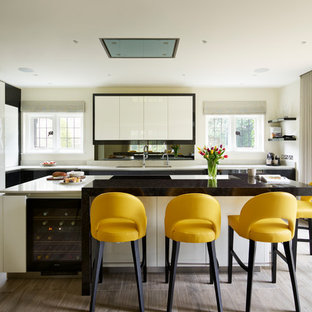 This is an example of a medium sized contemporary l-shaped kitchen in Hertfordshire with a submerged sink, flat-panel cabinets, white cabinets, an island, grey floors, mirror splashback and black appliances.