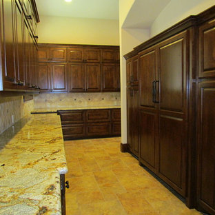 This is an example of a large country kitchen in Houston with raised-panel cabinets, dark wood cabinets, granite benchtops, porcelain splashback, stainless steel appliances, porcelain floors and with island.