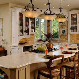Example of a large classic l-shaped dark wood floor open concept kitchen design in DC Metro with an undermount sink, glass-front cabinets, white cabinets, solid surface countertops, beige backsplash, stone tile backsplash, stainless steel appliances and an island