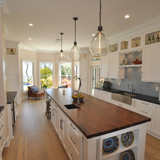 This is an example of a large transitional galley eat-in kitchen in Tampa with a farmhouse sink, shaker cabinets, white cabinets, granite benchtops, blue splashback, subway tile splashback, stainless steel appliances, medium hardwood floors and with island.