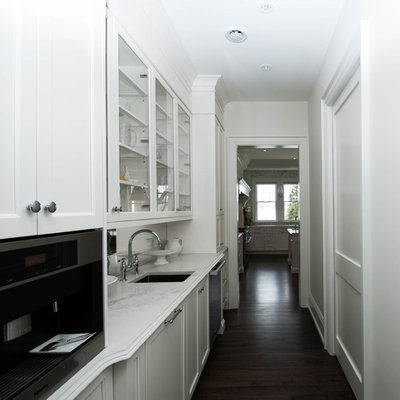 Huge elegant l-shaped dark wood floor and brown floor open concept kitchen photo in Other with an undermount sink, recessed-panel cabinets, white cabinets, quartz countertops, gray backsplash, marble backsplash, stainless steel appliances and an island