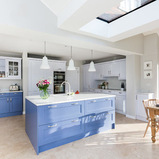 Large traditional single-wall open plan kitchen in Buckinghamshire with a double-bowl sink, shaker cabinets, blue cabinets, quartz worktops, white splashback, metro tiled splashback, black appliances, porcelain flooring, an island, beige floors and yellow worktops.