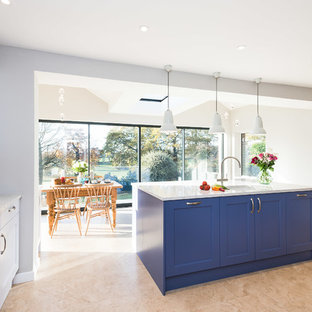 This is an example of a large classic single-wall open plan kitchen in Buckinghamshire with a double-bowl sink, shaker cabinets, blue cabinets, quartz worktops, white splashback, metro tiled splashback, black appliances, porcelain flooring, an island, beige floors and yellow worktops.