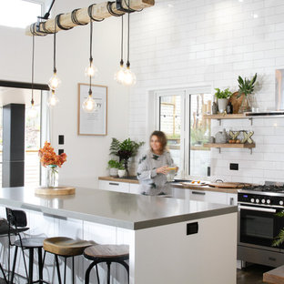 Photo of a mid-sized eclectic galley kitchen pantry in Other with a farmhouse sink, shaker cabinets, white cabinets, laminate benchtops, white splashback, subway tile splashback, stainless steel appliances, laminate floors, with island and brown floor.