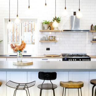 他の地域の中サイズのエクレクティックスタイルのおしゃれなキッチン (シェーカースタイル扉のキャビネット、白いキャビネット、ラミネートカウンター、白いキッチンパネル、サブウェイタイルのキッチンパネル、シルバーの調理設備、ラミネートの床、茶色い床、ドロップインシンク) の写真