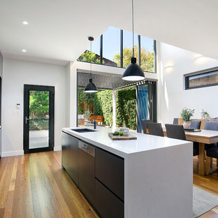 Photo of a contemporary galley open plan kitchen in Sydney with an undermount sink, flat-panel cabinets, black cabinets, marble benchtops, stainless steel appliances, medium hardwood floors, with island, brown floor and white benchtop.