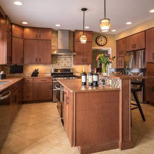 ニューヨークの広いインダストリアルスタイルのおしゃれなキッチン (アンダーカウンターシンク、フラットパネル扉のキャビネット、中間色木目調キャビネット、御影石カウンター、ベージュキッチンパネル、石タイルのキッチンパネル、シルバーの調理設備、セラミックタイルの床) の写真