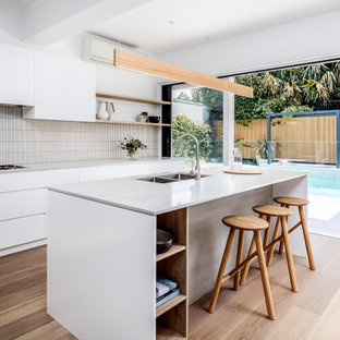 Beach style galley kitchen in Sydney with an undermount sink, flat-panel cabinets, white cabinets, white splashback, mosaic tile splashback, medium hardwood floors, with island, brown floor and white benchtop.