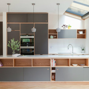 Photo of a mid-sized scandinavian single-wall kitchen in London with flat-panel cabinets, grey cabinets, beige floor, white benchtop, an undermount sink, white splashback, black appliances, light hardwood floors and a peninsula.