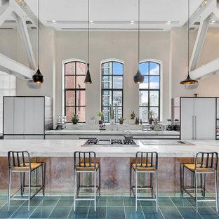Стильный дизайн: огромная параллельная кухня в стиле лофт с плоскими фасадами, белыми фасадами, мраморной столешницей, техникой под мебельный фасад, островом, зеленым полом и серой столешницей - последний тренд