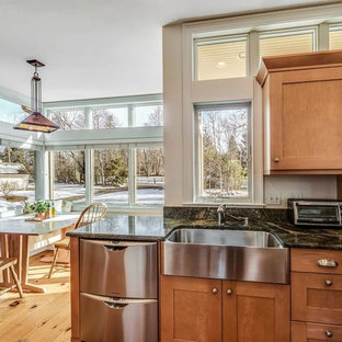 This is an example of a mid-sized contemporary u-shaped open plan kitchen in Boston with a farmhouse sink, shaker cabinets, light wood cabinets, granite benchtops, black splashback, stone slab splashback, stainless steel appliances, light hardwood floors, a peninsula and yellow floor.