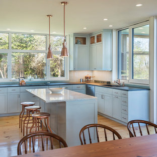 Design ideas for a large transitional u-shaped open plan kitchen in Providence with an undermount sink, shaker cabinets, turquoise cabinets, granite benchtops, glass tile splashback, stainless steel appliances, light hardwood floors, with island and beige floor.