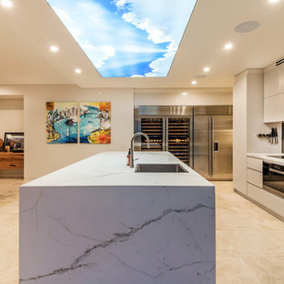 This is an example of a contemporary open plan kitchen in Sydney with a single-bowl sink, flat-panel cabinets, beige cabinets, metallic splashback, mirror splashback, black appliances, an island, beige floor and beige benchtop.