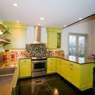 Mittelgroße Moderne Wohnküche ohne Insel in U-Form mit Doppelwaschbecken, Schrankfronten mit vertiefter Füllung, grünen Schränken, Betonarbeitsplatte, bunter Rückwand, Rückwand aus Glasfliesen, Küchengeräten aus Edelstahl, Betonboden und schwarzem Boden in Birmingham