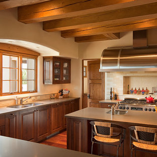 Large southwestern eat-in kitchen ideas - Large southwest u-shaped medium tone wood floor eat-in kitchen photo in Albuquerque with an undermount sink, raised-panel cabinets, medium tone wood cabinets, beige backsplash, stainless steel appliances, an island, quartz countertops and subway tile backsplash