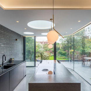 Inspiration for a medium sized modern galley kitchen/diner in London with an integrated sink, flat-panel cabinets, black cabinets, composite countertops, brick splashback, black appliances, concrete flooring, an island and grey floors.