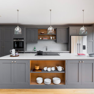 This is an example of a large traditional galley kitchen/diner in London with a submerged sink, shaker cabinets, grey cabinets, quartz worktops, white splashback, engineered quartz splashback, stainless steel appliances, medium hardwood flooring, an island and white worktops.