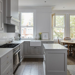 Small traditional l-shaped open plan kitchen in London with a farmhouse sink, grey cabinets, granite benchtops, grey splashback, granite splashback, panelled appliances, dark hardwood floors, with island, brown floor, grey benchtop, coffered and beaded inset cabinets.
