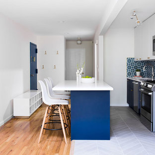 This is an example of a mid-sized modern single-wall open plan kitchen in New York with an undermount sink, flat-panel cabinets, blue cabinets, quartz benchtops, blue splashback, cement tile splashback, stainless steel appliances, porcelain floors, with island, grey floor and white benchtop.