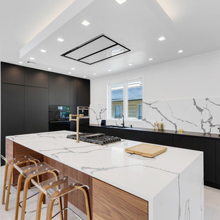 Contemporary l-shaped kitchen in New York with flat-panel cabinets, black cabinets, quartzite benchtops, marble floors, white floor, a double-bowl sink, white splashback, black appliances, with island and white benchtop.