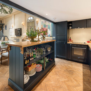 Medium sized traditional l-shaped kitchen in London with shaker cabinets, blue cabinets, wood worktops, beige splashback, black appliances, light hardwood flooring, an island, brown floors and brown worktops.