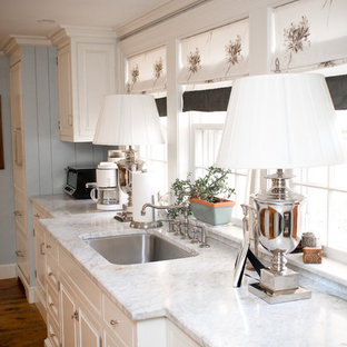 Eat-in kitchen - mid-sized farmhouse single-wall dark wood floor eat-in kitchen idea in Manchester with a single-bowl sink, marble countertops, white cabinets, stainless steel appliances and raised-panel cabinets