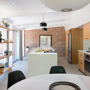 Photo of a mid-sized midcentury galley open plan kitchen in Other with an undermount sink, flat-panel cabinets, medium wood cabinets, quartz benchtops, green splashback, ceramic splashback, stainless steel appliances, porcelain floors, with island and grey floor.