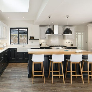 Photo of a traditional kitchen in Other with a belfast sink, recessed-panel cabinets, black cabinets, white splashback, stainless steel appliances, dark hardwood flooring, an island, brown floors and white worktops.