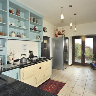 This is an example of a mid-sized traditional l-shaped separate kitchen in Vancouver with an undermount sink, open cabinets, blue cabinets, white splashback, porcelain splashback, stainless steel appliances, no island, quartz benchtops, limestone floors and beige floor.