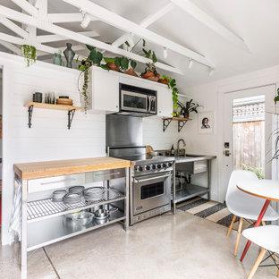 Cette image montre une petite cuisine américaine linéaire marine avec un évier 1 bac, un plan de travail en bois, une crédence blanche, une crédence en bois, un électroménager en acier inoxydable, béton au sol et un sol gris.