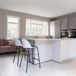 Imagen de cocina contemporánea, grande, abierta, con fregadero integrado, armarios con paneles lisos, puertas de armario grises, encimera de cuarcita, salpicadero blanco, suelo de baldosas de cerámica, una isla, suelo gris y encimeras blancas